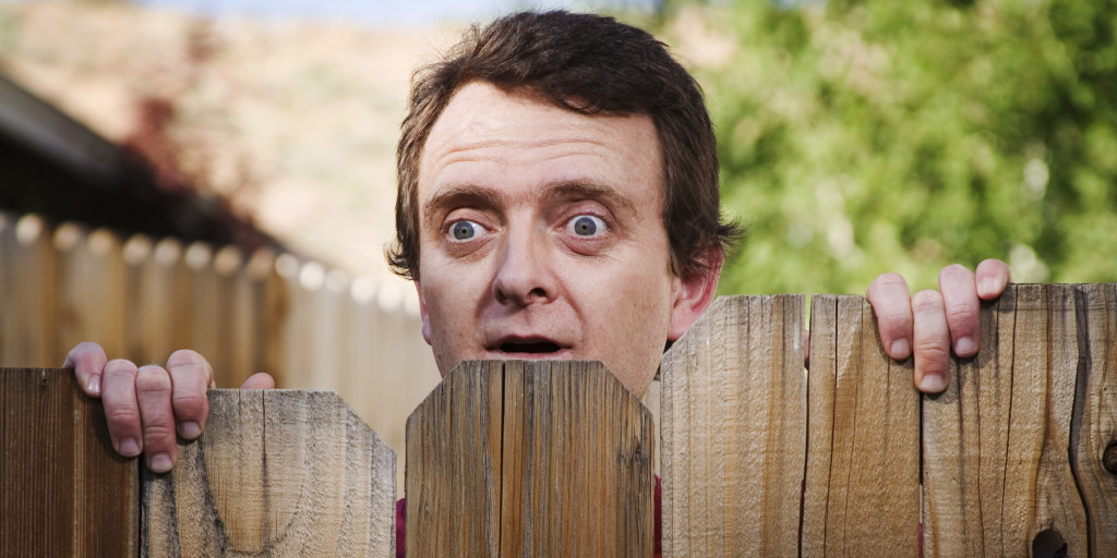 Man peeking over fence